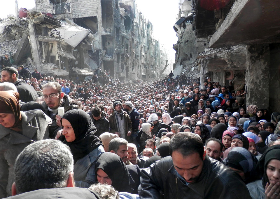 Photo - This picture taken on Jan. 31, 2014, and released by the United Nations Relief and Works Agency for Palestine Refugees in the Near East (UNRWA), shows residents of the besieged Palestinian camp of Yarmouk, queuing to receive food supplies, in Damascus, Syria. A United Nations official is calling on warring sides in Syria to allow aid workers to resume distribution of food and medicine in a besieged Palestinian district of Damascus. The call comes as U.N. Secretary General Ban Ki-Moon urged Syrian government to authorize more humanitarian staff to work inside the country, devastated by its 3-year-old conflict. (AP Photo/UNRWA)
