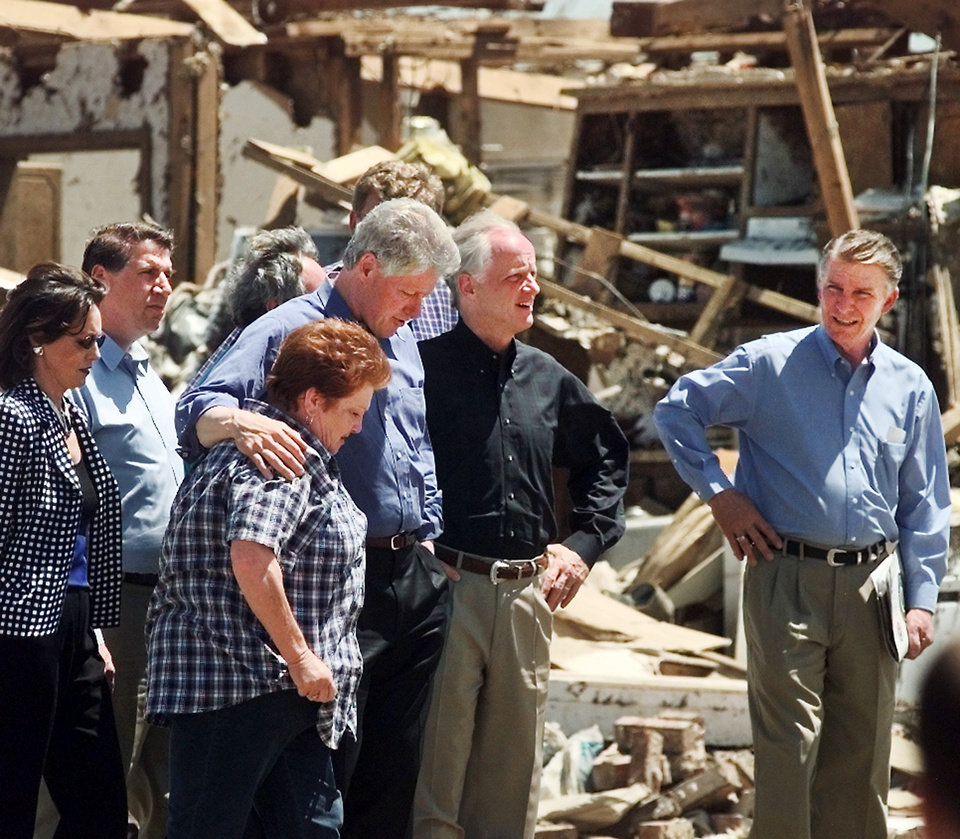 President Bill Clinton comforts homeowner Sherrill Evett while viewing damage to her home in the Del Aire housing addition in Del City Saturday morning.  With the President is Gov. Frank Keating and FEMA Director James Lee Witt, at right.  Behind them is Congressman Ernest Istook and First lady Cathy Keating.