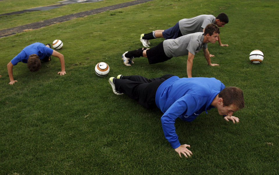 Photo - Players do push ups  during soccer practice at Piedmont High School in Piedmont, Okla., Wednesday, April 11, 2012. Photo by Nate Billings, The Oklahoman