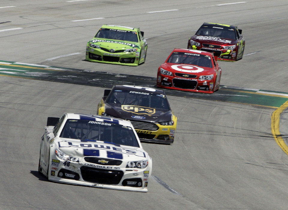 Photo - Jimmie Johnson (48) leads Carl Edwards (99) and the rest of the field early in the NASCAR Sprint Cup auto race at Kentucky Speedway in Sparta, Ky., Sunday, June 30, 2013.  (AP Photo/Garry Jones)