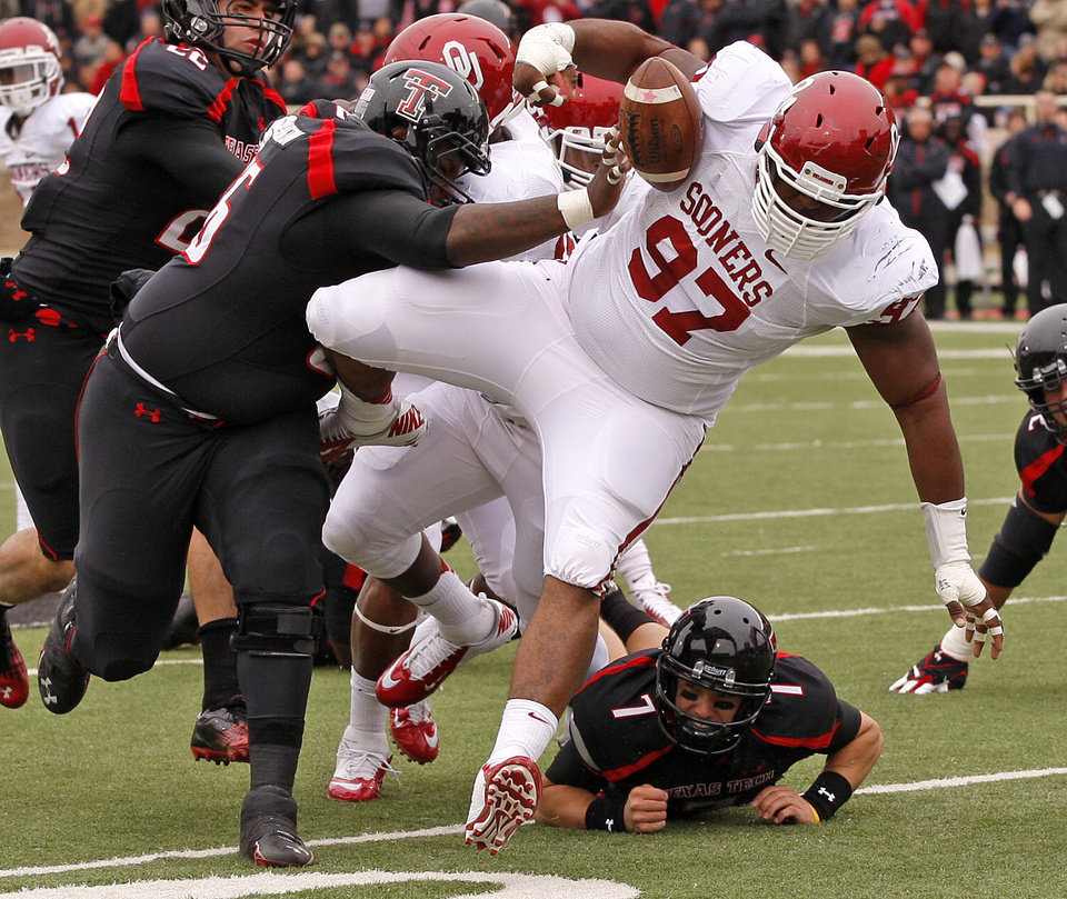 Photo - Oklahoma's Jamarkus McFarland (97) fumbles the ball after an interception beside Texas Tech's LaAdrian Waddle (65) during a college football game between the University of Oklahoma (OU) and Texas Tech University at Jones AT&T Stadium in Lubbock, Texas, Saturday, Oct. 6, 2012. Photo by Bryan Terry, The Oklahoman