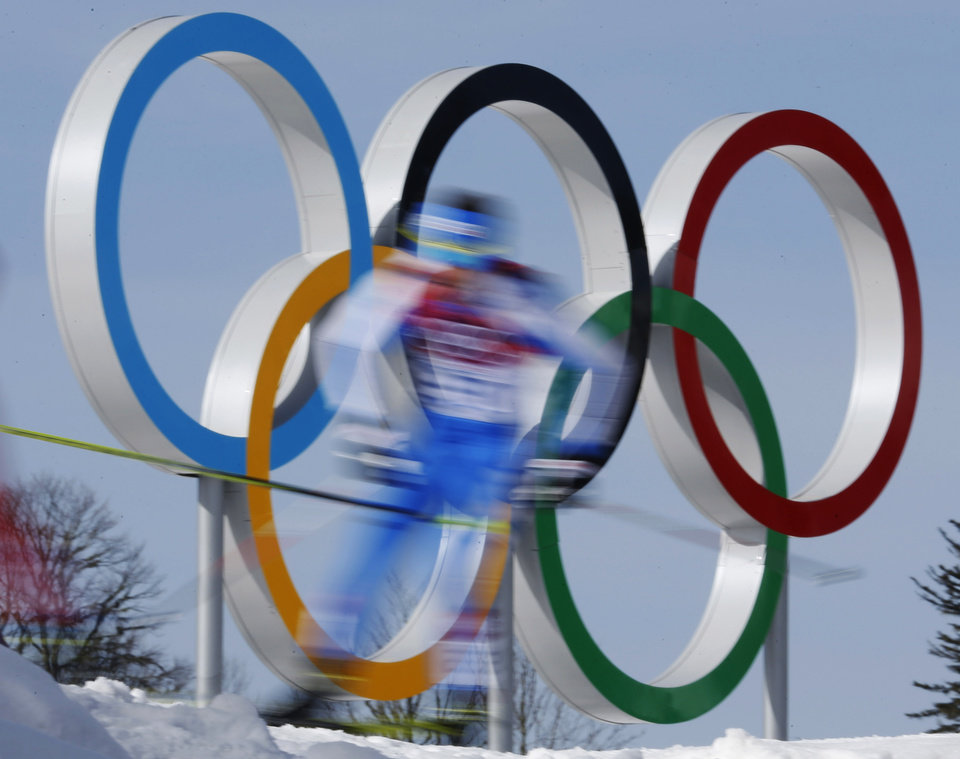 Photo - In this photo taken with slow shutter speed athletes pass by the Olympic rings during the men's 50K cross-country race at the 2014 Winter Olympics, Sunday, Feb. 23, 2014, in Krasnaya Polyana, Russia. (AP Photo/Dmitry Lovetsky)