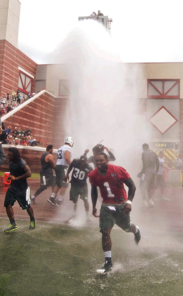 Photo - In this Aug. 13, 2014,  photo, New York Jets quarterback Michael Vick (1) runs from a large spray of water as players and coaches celebrated the final day of NFL football training camp in Cortland, N.Y. The Jets got soaked for a good cause. The team accepted the New England Patriots' Ice Bucket Challenge to their AFC East rivals and ended its last public practice at SUNY Cortland  by getting doused _ with help from the Cortlandville Fire Department. (AP Photo/The Cortland Standard, Bob Ellis )