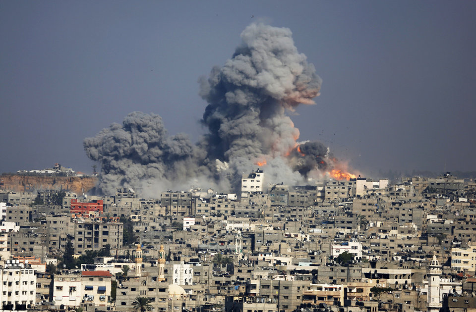 Photo - Smoke and fire from the explosion of an Israeli strike rise over Gaza City,  Tuesday, July 29, 2014. Israel escalated its military campaign against Hamas on Tuesday, striking symbols of the group's control in Gaza and firing tank shells that shut down the strip's only power plant in the heaviest bombardment in the fighting so far. The plant's shutdown was bound to lead to further serious disruptions of the flow of electricity and water to Gaza's 1.7 million people. (AP Photo/Hatem Moussa)