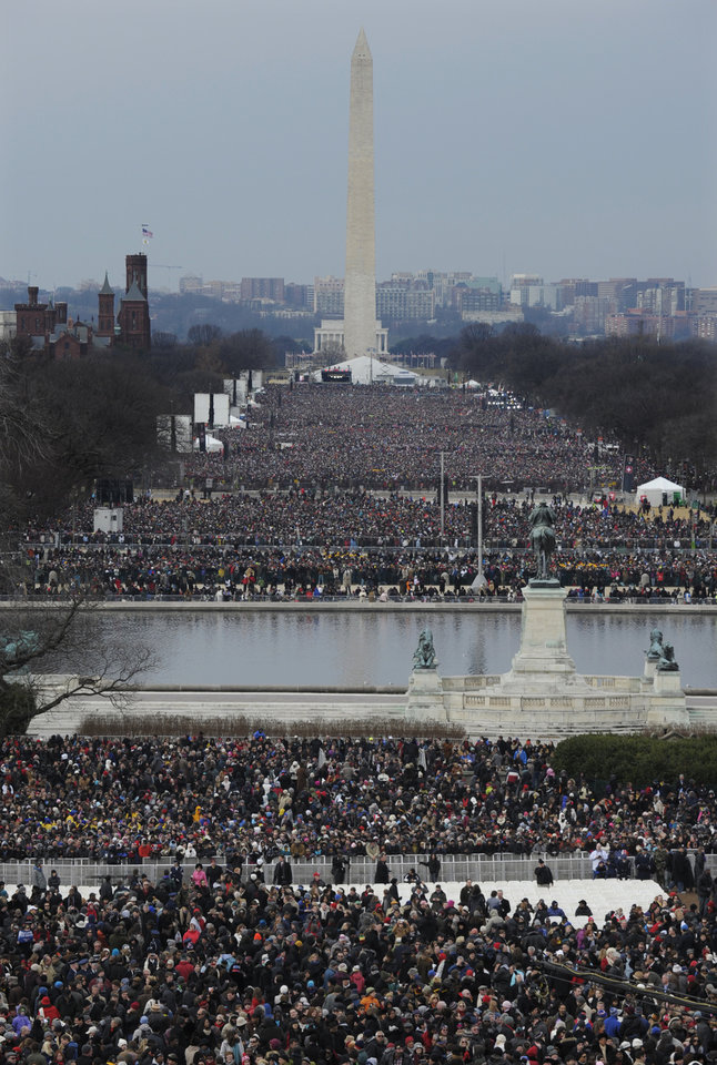Photo - Crowds congregate in The National Mall for the ceremonial swearing-in for President Barack Obama at the U.S. Capitol during the 57th Presidential Inauguration in Washington, Monday, Jan. 21, 2013. (AP Photo/Susan Walsh)