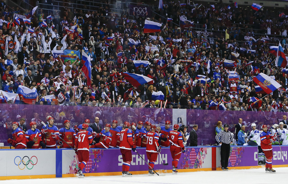 Photo - Fans cheer a goal by the team Russia against Slovenia in the second period of a men's ice hockey game at the 2014 Winter Olympics, Thursday, Feb. 13, 2014, in Sochi, Russia. (AP Photo/Julio Cortez)