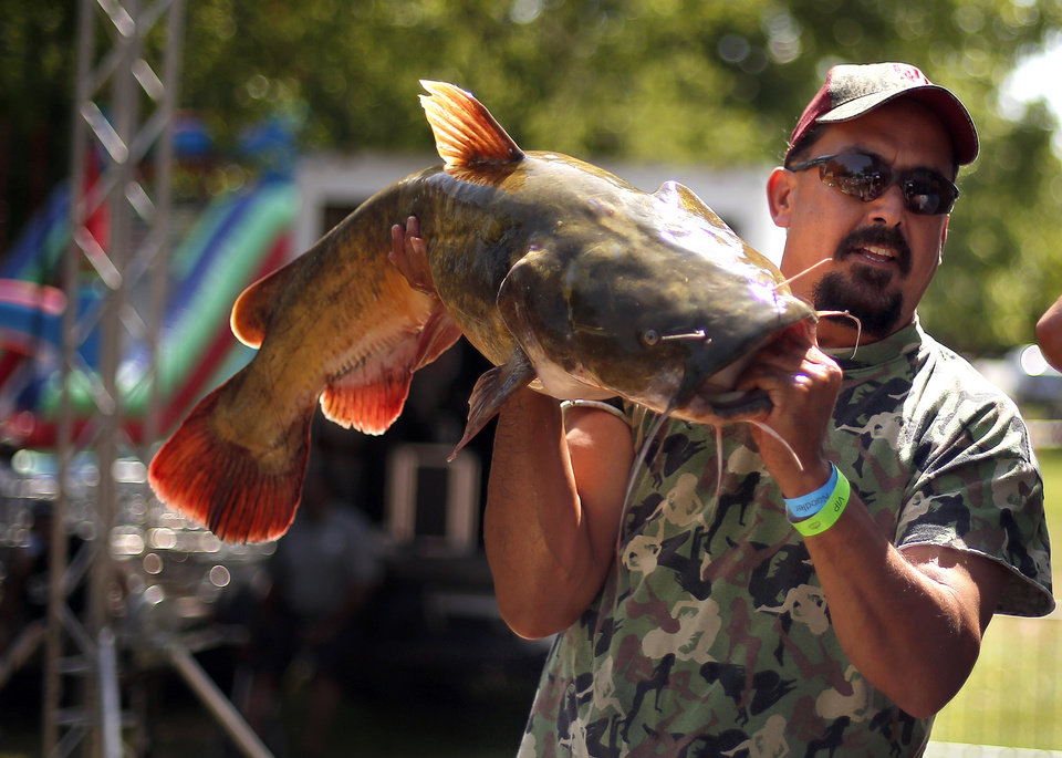 Photo - Luis Calvo, of Austin, Texas, holds his 33.5 pound catfish at the weigh-ins during the 14th annual Okie Noodling Tournament at Wacker Park in Pauls Valley, Okla., Saturday, June 22, 2013. Photo by Sarah Phipps, The Oklahoman