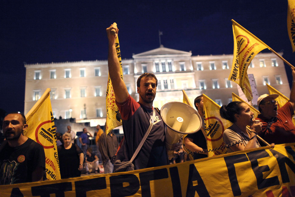 Photo -   Protesters chant slogans in front of the Greek parliament during a union anti-austerity rally a day before the visit by German Chancellor Angela Merkel, in Athens on Monday, Oct. 8, 2012. Greek police have increased security and are preparing to close down large sections of the capital Athens to contain protests against Germany's Chancellor, Angela Merkel, who is visiting the city Tuesday for talks with the country's Prime Minister Antonis Samaras.(AP Photo/Petros Giannakouris)