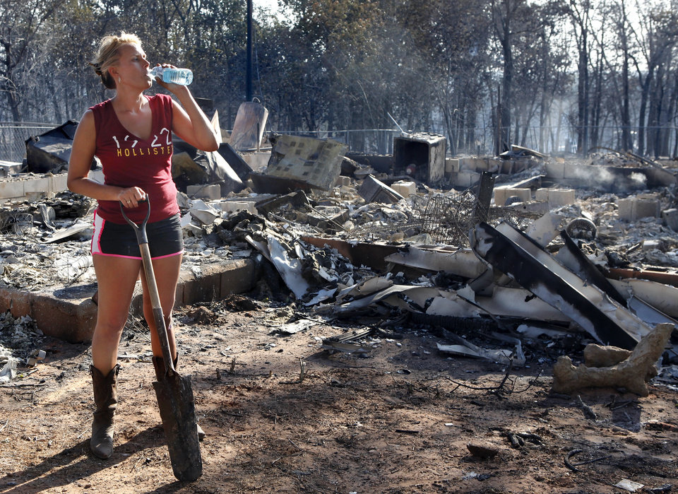 Photo - Brandy West drinks water in front of the burned home of her mother.  West was on the property shortly after sunrise to begin searching for salvageable items, mostly documents and her mother's belongings  from inside the three bedroom frame house at 1006. S. Douglas Street. Her parents had lived in this house for 30 years before fire destroyed it.  Residents  in Luther were allowed to return to the their homes early Saturday, Aug. 4, 2012, after they fled a rapidly moving wildfire yesterday that consumed at least seven structures on South Dogwood Street, leaving smoldering ashes where family homes once stood.  