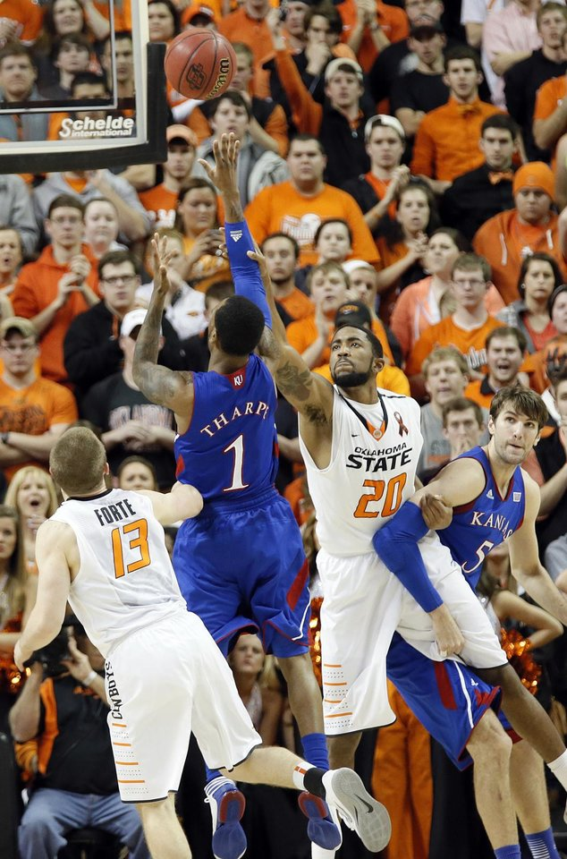 Photo - Kansas' Naadir Tharpe (1) puts up a shot over Oklahoma State 's Michael Cobbins (20) during the college basketball game between the Oklahoma State University Cowboys (OSU) and the University of Kanas Jayhawks (KU) at Gallagher-Iba Arena on Wednesday, Feb. 20, 2013, in Stillwater, Okla. Photo by Chris Landsberger, The Oklahoman