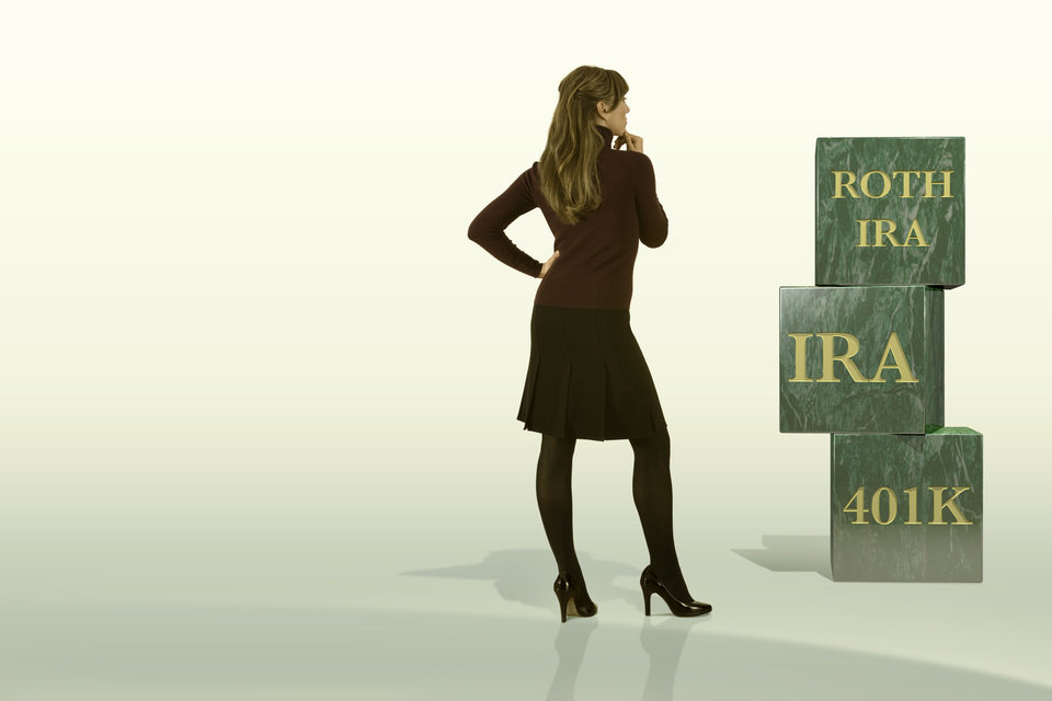 Photo - Businesswoman looking at blocks for Roth IRA, IRA, and 401k