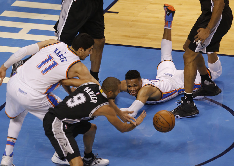 Photo - Oklahoma City's Russell Westbrook (0) looks on as San Antonio's Tony Parker (9) and Enes Kanter (11) scramble of the ball during Game 4 of the Western Conference semifinals between the Oklahoma City Thunder and the San Antonio Spurs in the NBA playoffs at Chesapeake Energy Arena in Oklahoma City, Sunday, May 8, 2016. Photo by Sarah Phipps, The Oklahoman