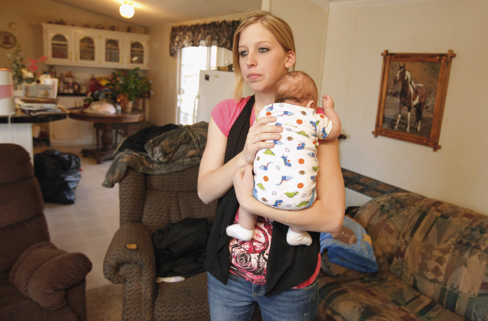 Sarah McKinley, 18, and her son Justin in the living room of her mobile home on Wednesday, Jan. 4, 2012, in Blanchard, Okla.  McKinley shot and killed an intruder who broke through the front door.  Photo by Steve Sisney, The Oklahoman