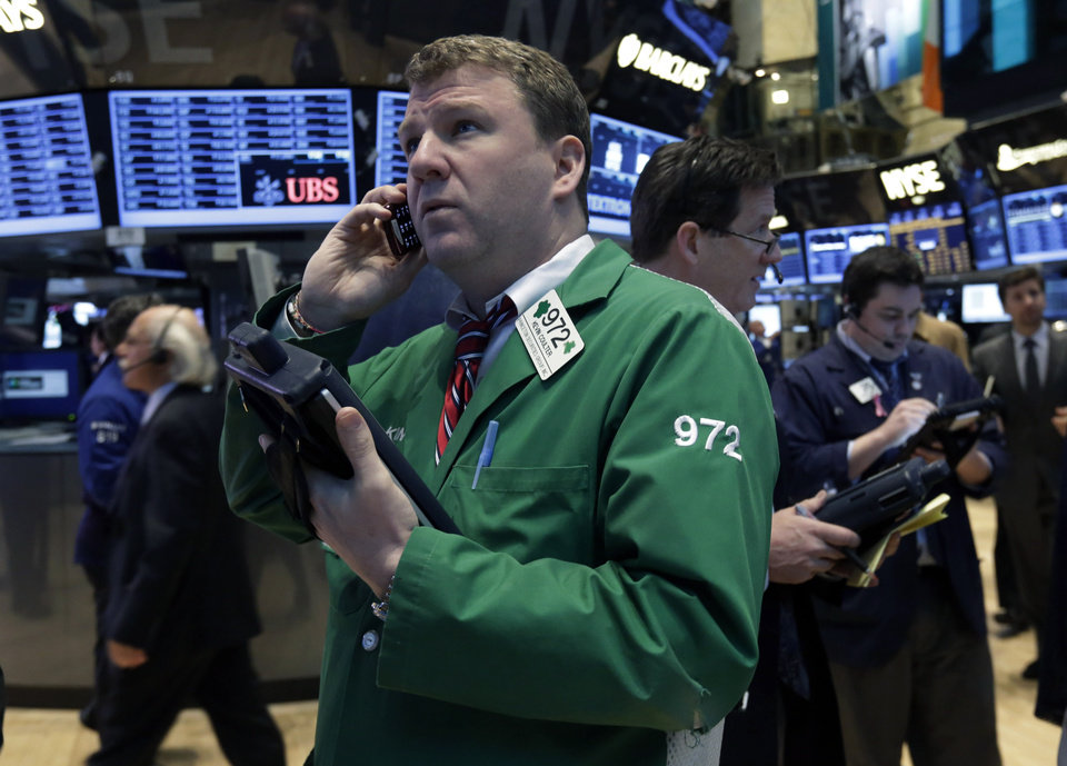 Kevin Coulter, foreground left, works with fellow traders on the floor of the New York Stock Exchange Tuesday, Jan. 22, 2013. Stocks are wavering in early trading on Wall Street as U.S. companies turn in a mixed batch of earnings reports. (AP Photo/Richard Drew)