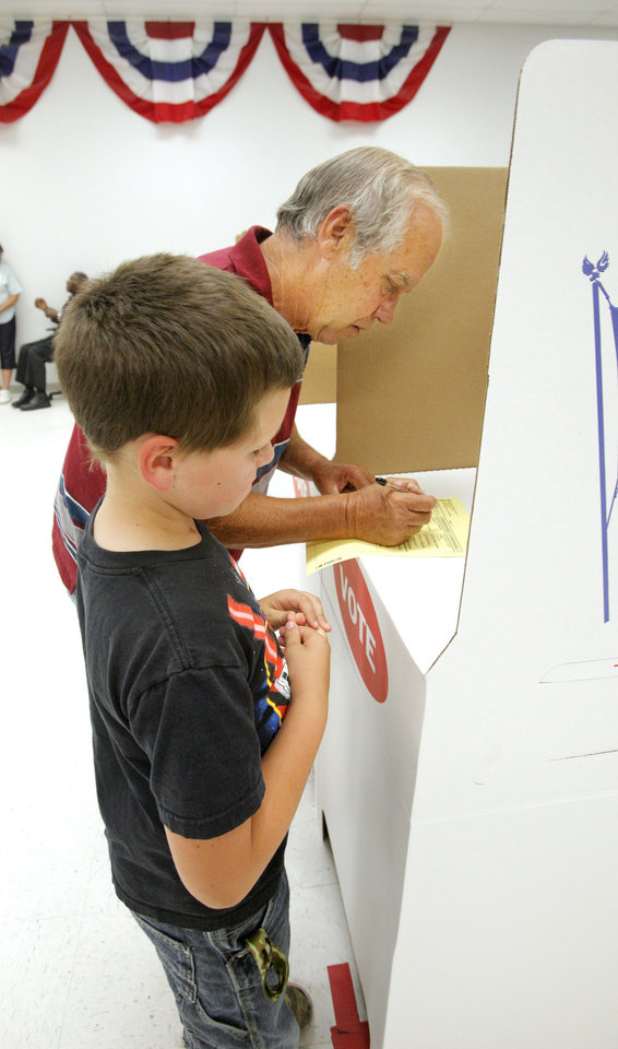 Xavier Gass, age 9 from Choctaw, watches as his grandfather Jimmy R. Gass, also from Choctaw, looks over the ballot in a voting booth during early voting at the Oklahoma County Election Board in Oklahoma City Monday, June 25, 2012.  Photo by Paul B. Southerland, The Oklahoman