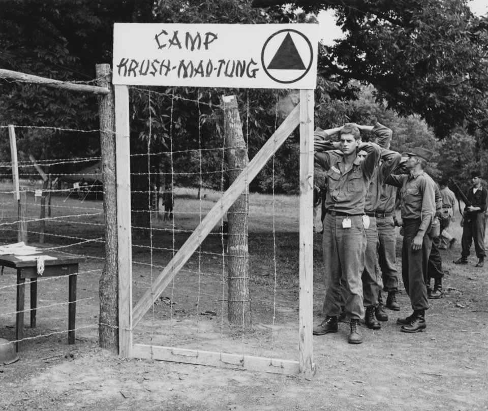 Photo - Oklahoman learn what it's like to be a communist prisoner in realistic exercises at 45th Infantry Division summer camp.  In the left picture the Thunderbirds are marched into Camp Krush Mao-Tung for interrogation.  Photographer and date unknown.  Published in The Daily Oklahoman 08/15/1963.