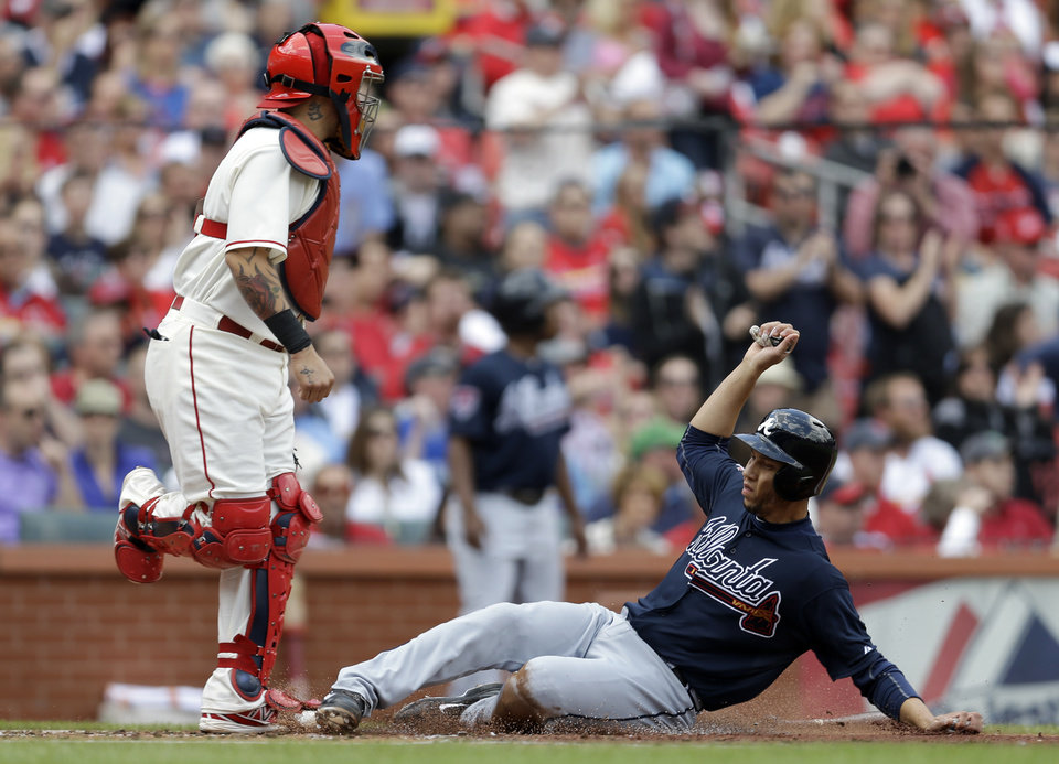 Photo - Atlanta Braves' Andrelton Simmons, right, scores on a throwing error by St. Louis Cardinals second baseman Kolten Wong as Cardinals catcher Yadier Molina, left, stands by during the second inning of a baseball game on Saturday, May 17, 2014, in St. Louis. (AP Photo/Jeff Roberson)