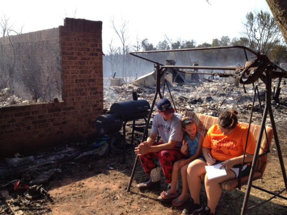 Residents survey the aftermath of wildfires that spread through Luther and Cleveland County on Friday. About 25 homes and a day care center were destroyed by the fire in Luther. In Cleveland County, several homes were destroyed by the fire near Norman, Slaughterville and Noble. Photo by James Beckel, The Oklahoman
