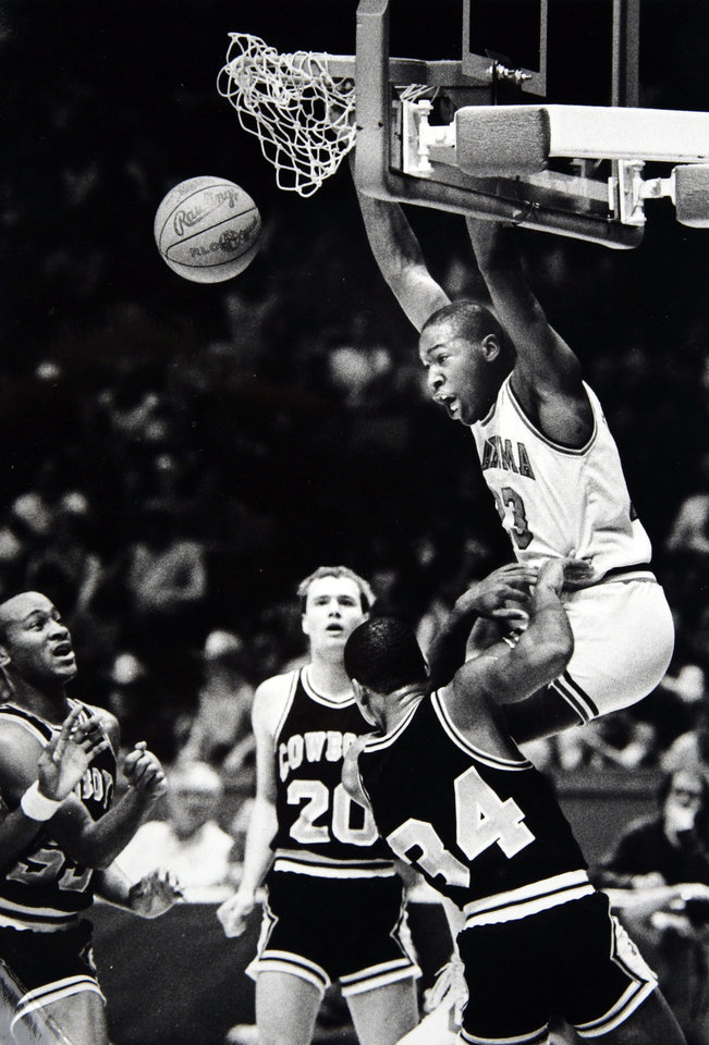 Photo - Former OU basketball player Wayman Tisdale. Wayman Tisdale ripples the net with a big dunk for two of his 36 points in front of OSU's Raymond Crenshaw (left), Bill Self (20) and Charles Williams (34). Staff Photo by Doug Hoke. Photo taken 1/24/1984, published 1/25/1984, 1/26/1984, 3/17/1996. ORG XMIT: KOD