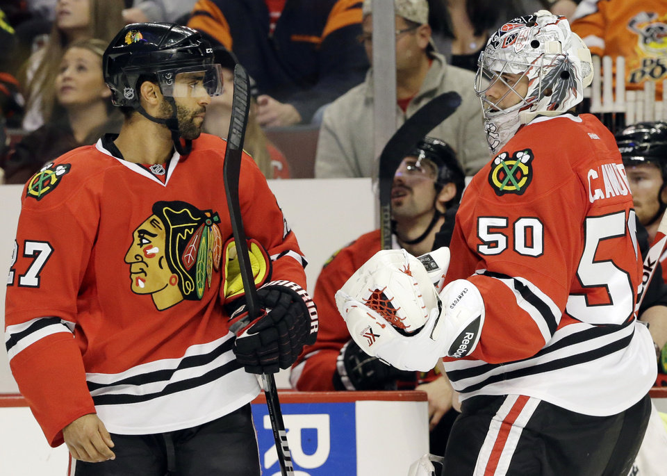 Photo - Chicago Blackhawks goalie Corey Crawford, right, talks with Johnny Oduya during the first period of an NHL hockey game against the Phoenix Coyotes in Chicago, Thursday, Nov. 14, 2013. (AP Photo/Nam Y. Huh)