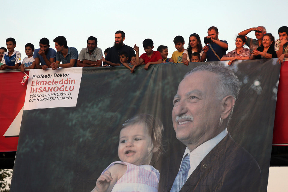Photo - People listen to the main opposition candidate  Ekmeleddin Ihsanoglu, as he addresses a rally in Istanbul, Turkey, Saturday, Aug. 9, 2014. Some 53 million Turks go the polls on Sunday to choose their 12th president in an election considered a turning point for the country of 76 million people, with Prime Minister Recep Tayyip Erdogan vying for the position he has pledged to transform from a symbolic role into a position of power. Ekmeleddin Ihsanoglu, the former chief of the Organization of Islamic Cooperation, and Kurdish politician Selahattin Demirtas are also running. (AP Photo/Volkan Yildirim)