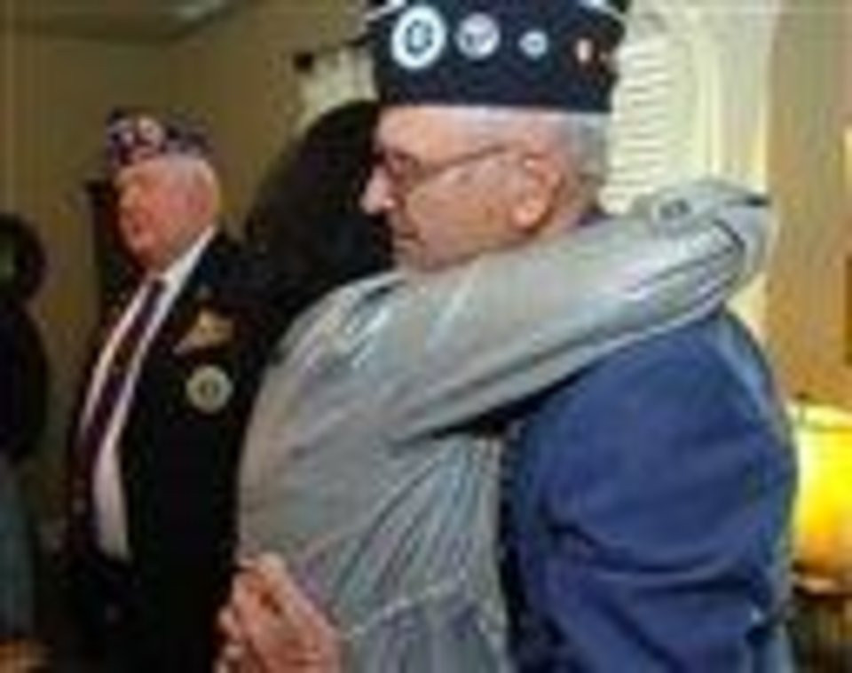 Judy Krause-Mobley gives a big hug to Grayson Tate after he read a letter from then-president Harry Truman to the family of Veer Krause on his receiving the Purple Heart during the Korean War during a ceremony in the family house in Gurley, Ala. Krause, a Korean War veteran, had his Purple Heart bought for a dollar at a garage sale in Illinois is being returned to a Gurley relative almost 60 years after he died in battle. It was returned to the family during a quiet family ceremony in Gurley. (AP Photo/The Huntsville Times, Eric Schultz)