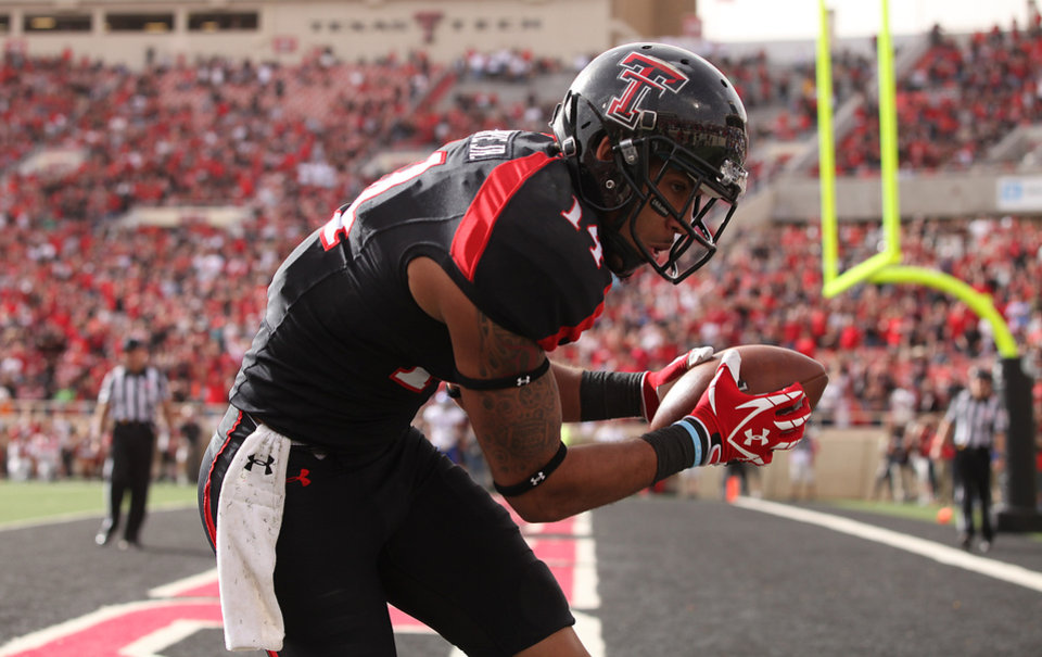 Texas Tech's Darrin Moore makes a touchdown catch against Kansas during their NCAA college football game in Lubbock, Texas, Saturday, Nov. 10, 2012. (AP Photo/Lubbock Avalanche-Journal, Zach Long) LOCAL TV OUT