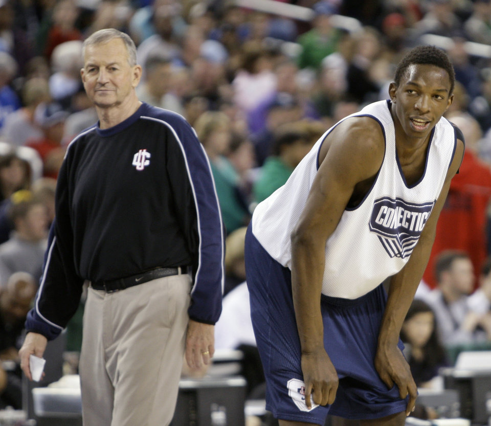 Photo - Connecticut's Hasheem Thabeet stands on the court as coach Jim Calhoun, left, looks on during a practice session at the men's Final Four NCAA college basketball tournament, Friday, April 3, 2009, in Detroit. (AP Photo/Eric Gay)  ORG XMIT: FF137
