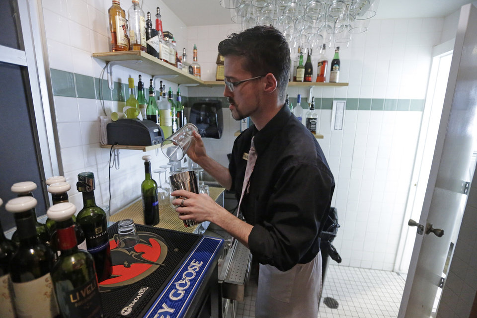 "Manager Dustin Humes fixes a drink in a small room which is out of the view of patrons at Vivace Restaurant Monday, Feb. 26, 2013, in Salt Lake City. Utah lawmakers are considering repealing a law that requires restaurants to mix alcoholic drinks out of view from patrons. Commonly known as ""Zion curtains,"" the mandate went into effect for restaurants in 2010 as part of a compromise when lawmakers lifted a mandate for bars to operate as members-only social clubs. The rule does not apply to restaurants that opened before 2010. A House committee is expected to discuss the bill Wednesday. Restaurant owners and tourism officials say the law is unnecessary and hinders tourism. But some lawmakers say that removing the mandate could encourage underage drinking and influence customers to drink too much. (AP Photo/Rick Bowmer)"