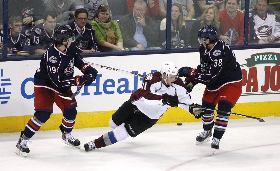 Photo - Colorado Avalanche's Jamie McGinn (11) loses his footing between Columbus Blue Jackets' Ryan Johansen (19) and Boone Jenner (38) during the third period of an NHL hockey game, Tuesday, April 1, 2014, in Columbus, Ohio. (AP Photo/Mike Munden)