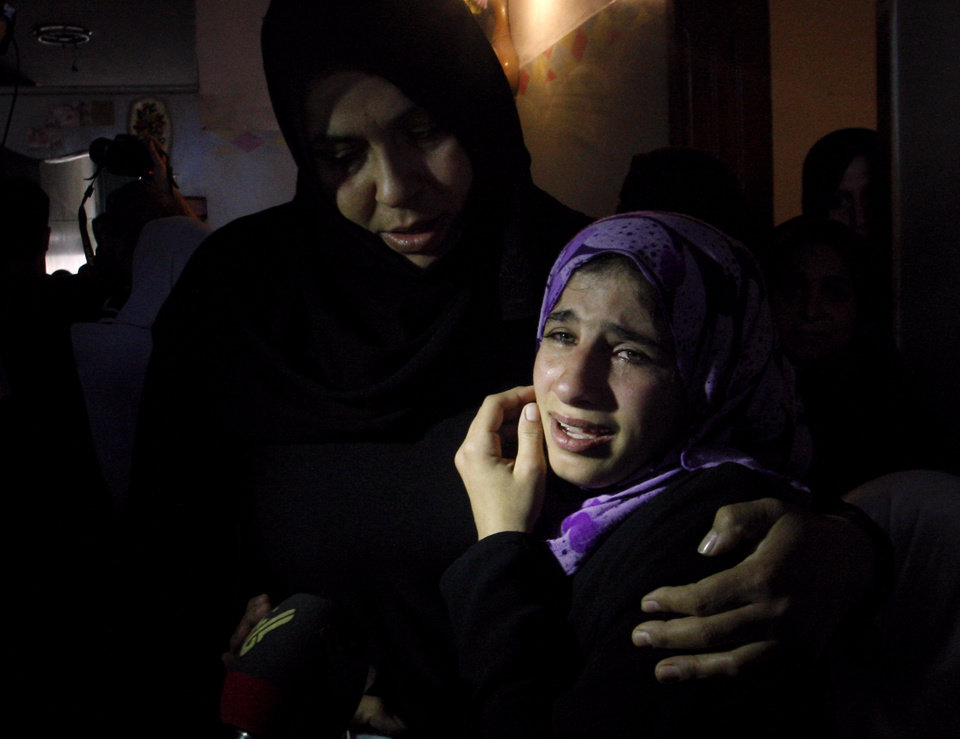 Photo -   A Palestinian woman comforts another during the funeral of Matar Abu Ata, 20, killed in an overnight Israeli airstrike in Gaza City, Sunday, Nov. 11, 2012. While cross-border fighting is a common occurrence, hostilities spiraled sharply over the weekend, with bombardments from Gaza causing rare Israeli casualties and Israeli strikes killing at least six Palestinians. (AP Photo/Hatem Moussa)