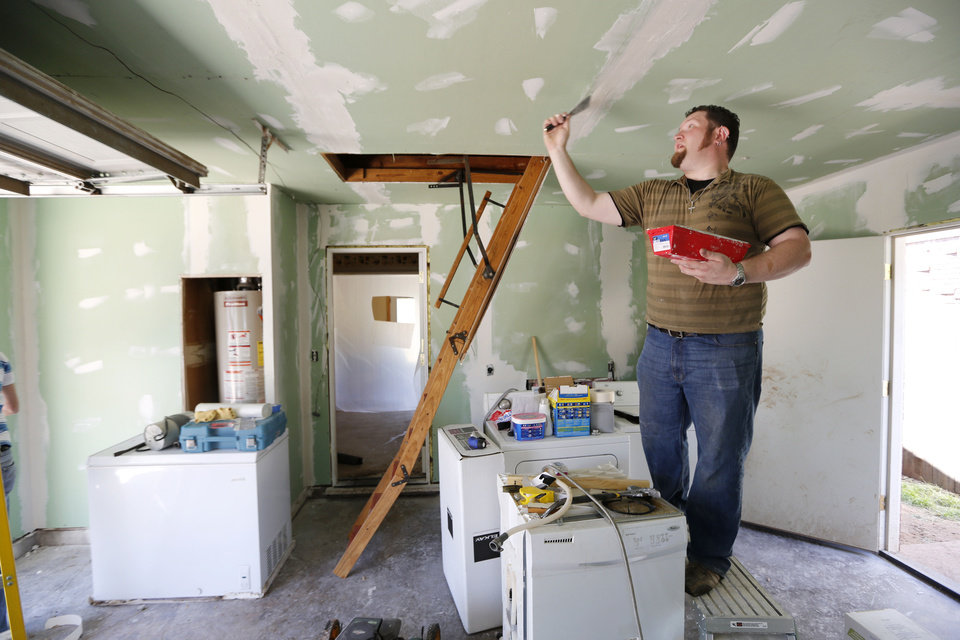 Photo - Andrew Rapson applies joint compound in the garage of Iraq War veteran Josh Lozier's home in Midwest City. Rapson and other volunteers from Home Depot were refurbishing Lozier's house. Photo By Steve Gooch, The Oklahoman  Steve Gooch - The Oklahoman