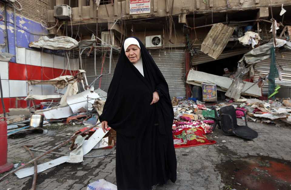 Photo - An Iraqi woman pauses at the site of a car bomb attack in central Baghdad's busy commercial Karradah neighborhood, Iraq, Wednesday, Aug 13, 2014. On Tuesday night, a car bomb exploded in the commercial district of Karrada, killing and wounded scores of people. (AP Photo/Hadi Mizban)