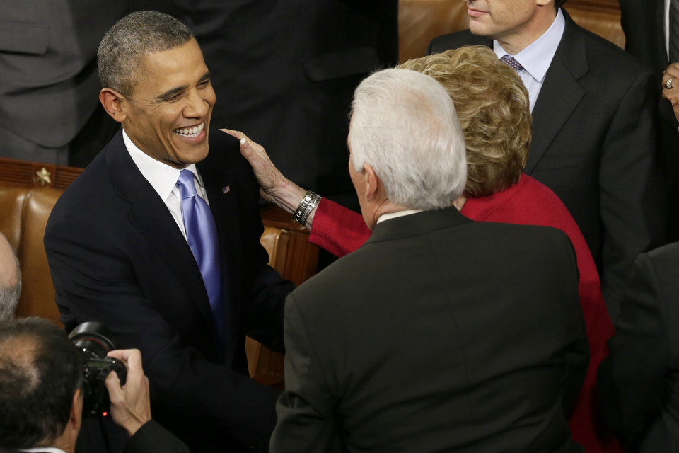 Photo - President Barack Obama is greeted before giving his State of the Union address on Capitol Hill in Washington, Tuesday Jan. 28, 2014. (AP Photo/J. Scott Applewhite)