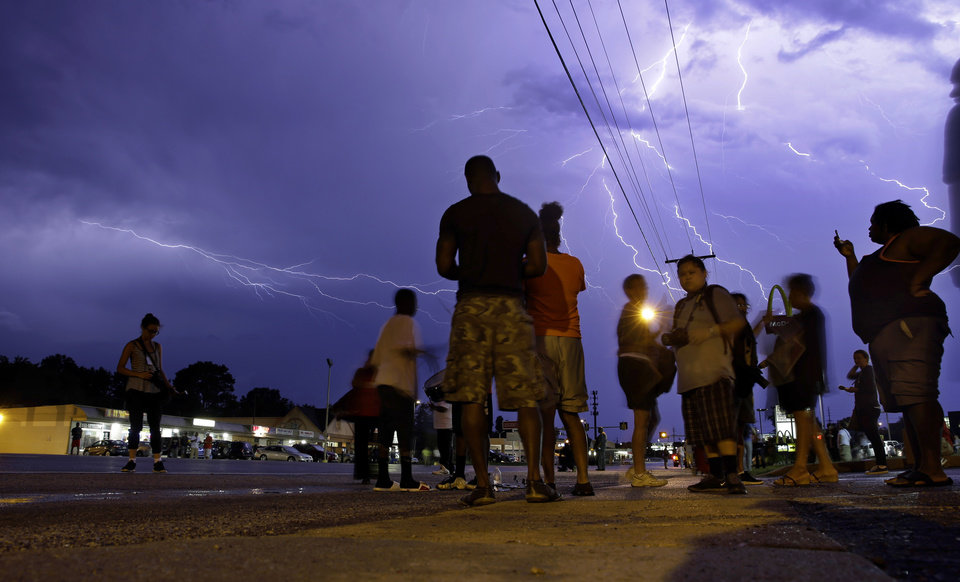 Photo - Protesters stand in the street as lightning flashes in the night sky in Ferguson, Mo. on Wednesday, Aug. 20, 2014. A grand jury has begun hearing evidence as it weighs possible charges against the Ferguson police officer who fatally shot 18-year-old Michael Brown. (AP Photo/Jeff Roberson)