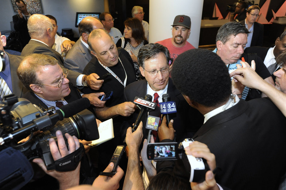Photo - Tom Werner, center, part owner of the Boston Red Sox and candidate to serve as next commissioner of Major League Baseball, speaks to reporters after team owners elected Rob Manfred, not pictured, as the next commissioner of Major League Baseball during an owners quarterly meeting in Baltimore Thursday, August 14, 2014. (AP Photo/Steve Ruark)