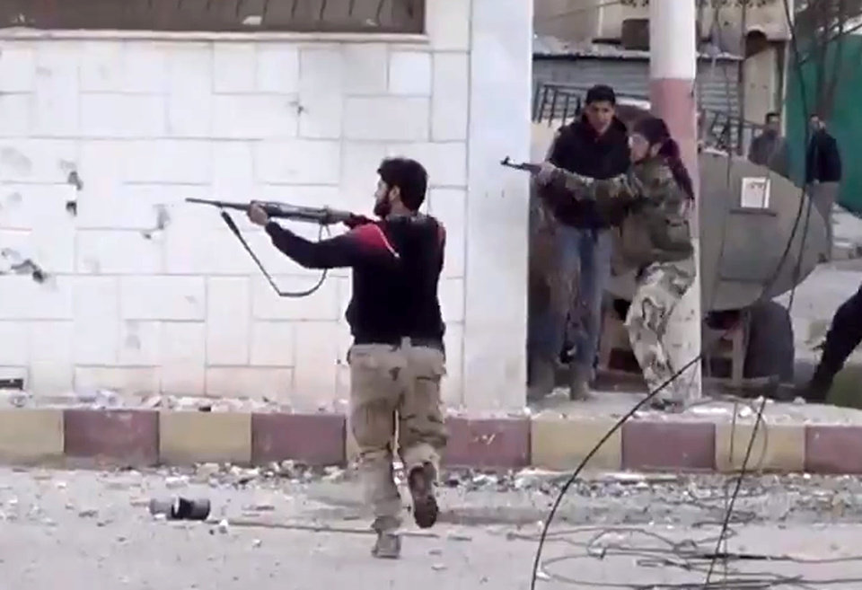 Photo - In this image taken from video obtained from the Shaam News Network, which has been authenticated based on its contents and other AP reporting, Free Syrian Army fighters fire at Syrian army soldiers during a fierce firefight in Daraa al-Balad, Syria, Monday March 18, 2013. Two years after the anti-Assad uprising began, the conflict has become a civil war, with hundreds of rebel group fighting Assad's forces across Syria and millions of people pushed from their homes by the violence. The U.N. says more than 70,000 people have been killed. (AP Photo/Shaam News Network via AP video)