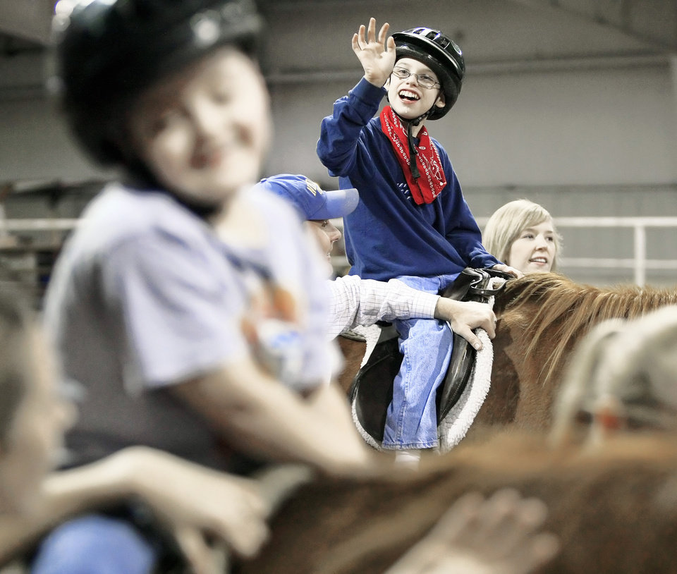 Photo - Braden Clary, 14, of Jay, waves to his parents as he rides Ajax at Northeastern Oklahoma A&M Arena in Miami.  Photo by STEPHEN HOLMAN, TULSA WORLD