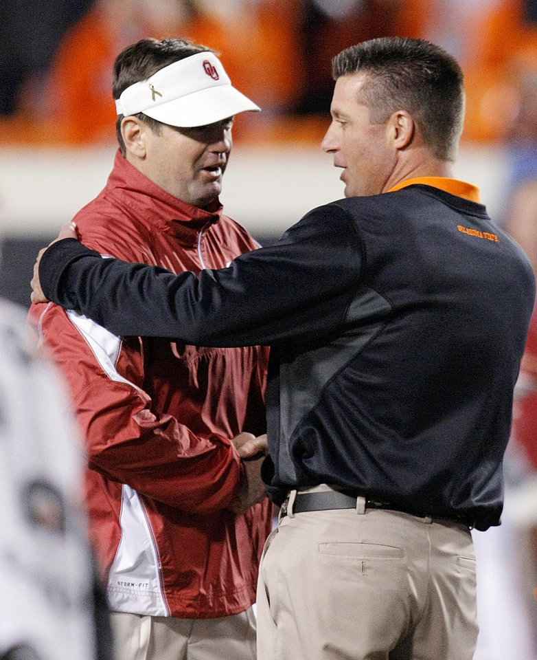 Photo - OU head coach Bob Stoops, left, and OSU head coach Mike Gundy shake hands before the Bedlam college football game between the University of Oklahoma Sooners (OU) and the Oklahoma State University Cowboys (OSU) at Boone Pickens Stadium in Stillwater, Okla., Saturday, Nov. 27, 2010. Photo by Nate Billings, The Oklahoman