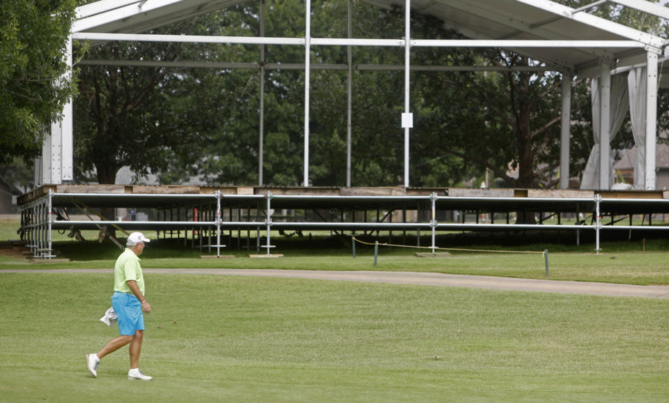 Photo - A golfer walks in front of temporary buildings that have been erected on the course at Oak Tree National Country Club in preparation for the 2014 U.S. Senior Open, held in July, on June 12, 2014. Photo by KT King/The Oklahoman