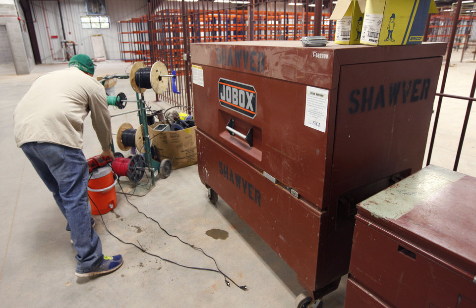 Photo -  A Miller Tippens Construction worker puts construction equipment in a metal locking tool box in Oklahoma City. Photo by Paul Hellstern, The Oklahoman   PAUL HELLSTERN -  Oklahoman