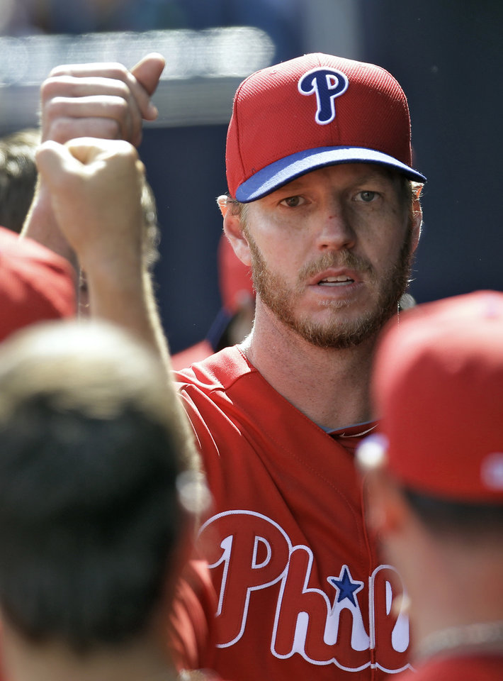 Philadelphia Phillies pitcher Roy Halladay high-fives teammates after leaving their game against the New York Yankees in the third inning of a spring training baseball game, Friday, March 1, 2013, in Tampa, Fla. (AP Photo/Chris O'Meara)