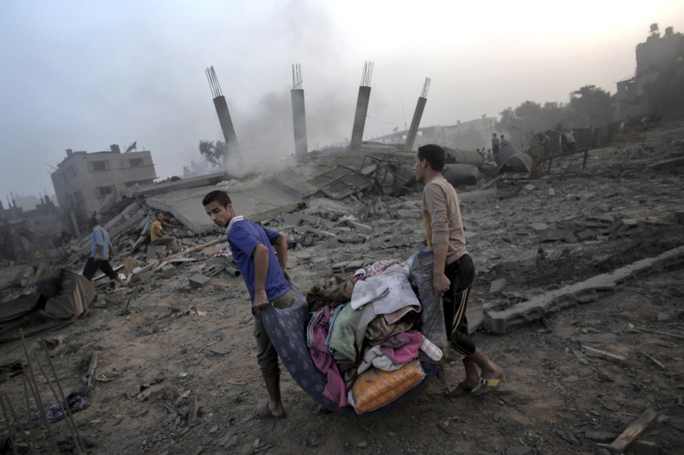Photo - Palestinians try to salvage what they can of their belongings from the rubble of a house destroyed by an overnight Israeli airstrike in Gaza City Tuesday, July 8, 2014.  Israel launched what could be a long-term offensive against the Hamas-ruled Gaza Strip on Tuesday, the military said, striking at least 50 sites in Gaza by air and sea and mobilizing troops for a possible ground invasion in order to quell rocket attacks on Israel. (AP Photo/Khalil Hamra)