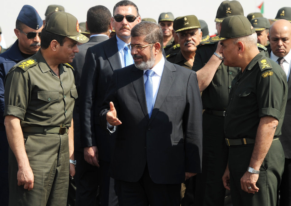 Photo - FILE - In this Wednesday, Oct. 10, 2012 file photo provided by the Egyptian Presidency, Egyptian President Mohammed Morsi, center, speaks with Minister of Defense, Lt. Gen. Abdel-Fattah el-Sissi, left, at a military base in Ismailia, Egypt. Washington's decision to withhold millions of dollars in mostly military aid to Egypt fuels anti-U.S. sentiment in the most populous Arab nation along with the perception that Washington supports Morsi, the Islamist president the military ousted in a July coup. Heightening those sentiments could boost the popularity of El-Sissi, whom the U.S. is trying to pressure to ensure a transition to democracy. (AP Photo/Egyptian Presidency, File)
