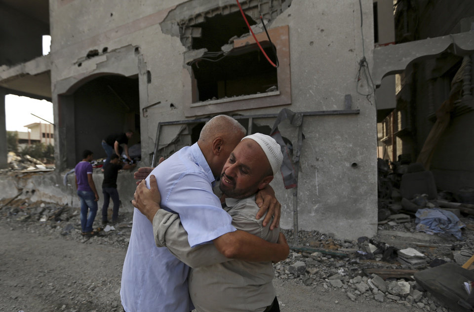 Photo - Palestinians give greetings in front of the damaged house of Gaza's police chief Taysir al-Batsh after it was hit by an Israeli missile strike in Gaza City, Sunday, July 13, 2014. The strike that hit the home and damaged a nearby mosque as evening prayers ended Saturday, killed at least 18 people, wounded 50 and left some people believed to be trapped under the rubble, said Palestinian Health Ministry official Ashraf al-Kidra. (AP Photo/Hatem Moussa