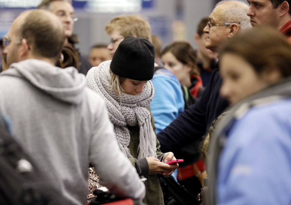 Photo - A woman checks her cell phone as she waits at the check-in line in Terminal 3 at O'Hare International Airport in Chicago on Sunday, Jan. 5, 2014. Illinois residents are digging out of more snow and preparing for bitterly cold temperatures. Sunday night temperatures are predicted to drop drastically, to about minus 20 degrees. (AP Photo/Nam Y. Huh)
