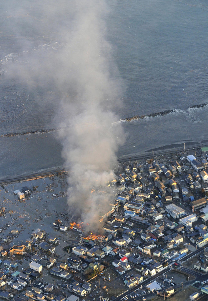 Photo - Fire smokes billow from residences as a coastal area is flooded by waters after a tsunami in Iwaki, Fukushima prefecture (state), Japan, Friday, March 11, 2011. The powerful tsunami spawned by the largest earthquake in Japan's recorded history slammed the eastern coast Friday, sweeping away boats, cars, homes and people as widespread fires burned out of control. (AP Photo/Kyodo News) JAPAN OUT, MANDATORY CREDIT, FOR COMMERCIAL USE ONLY IN NORTH AMERICA ORG XMIT: TOK807