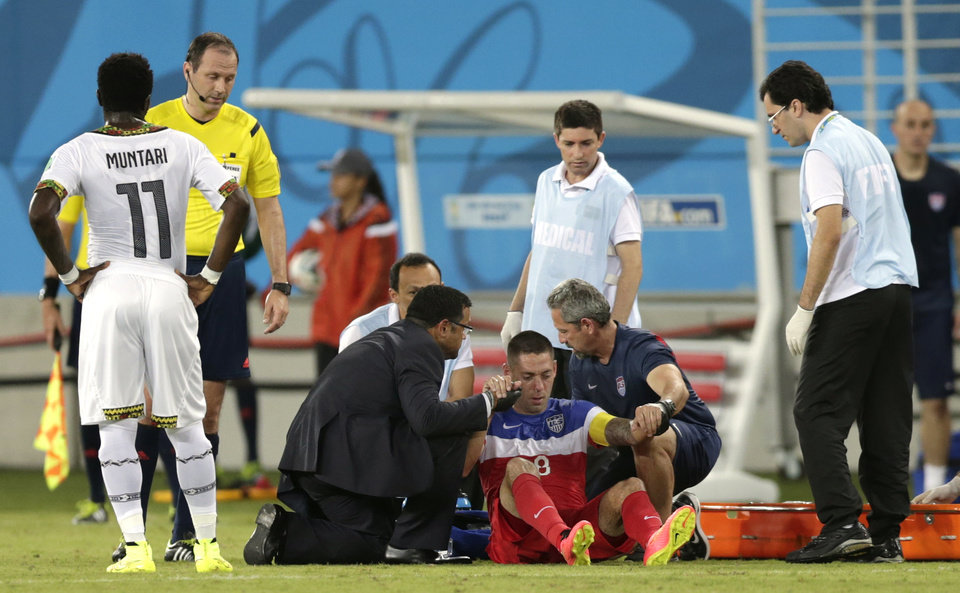 Photo - United States' Clint Dempsey, centre on ground, is helped to his feet after he was injured during the group G World Cup soccer match between Ghana and the United States at the Arena das Dunas in Natal, Brazil, Monday, June 16, 2014.  (AP Photo/Dolores Ochoa)