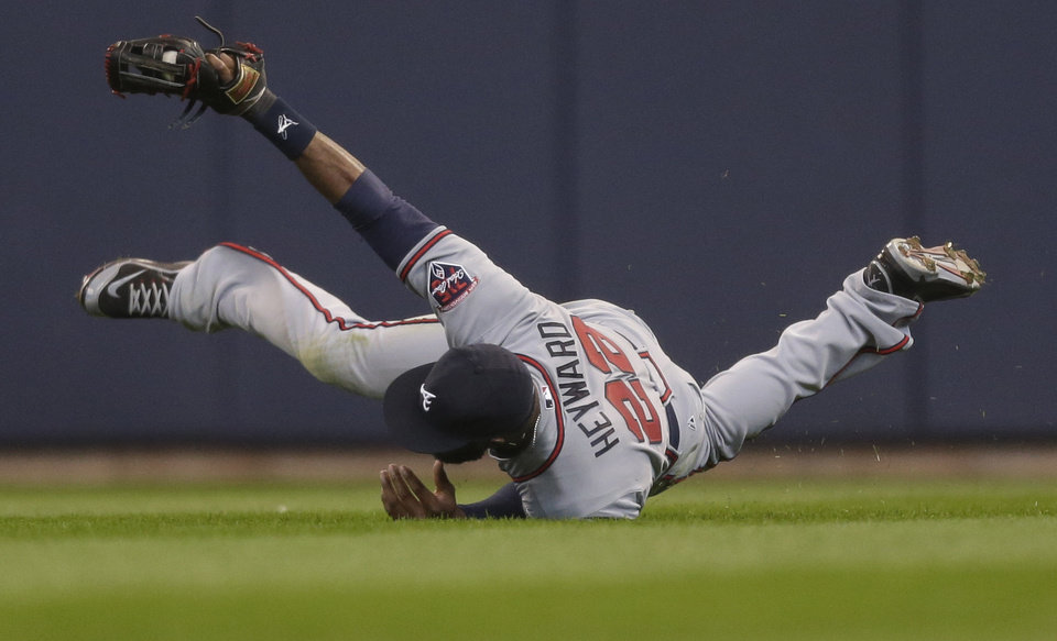 Atlanta Braves' Jason Heyward makes a sliding catch on a ball hit by Milwaukee Brewers' Carlos Gomes during the ninth inning of a baseball game Wednesday, April 2, 2014, in Milwaukee. Atlanta won 1-0. (AP Photo/Jeffrey Phelps)