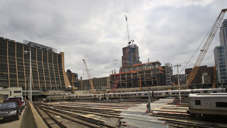 Photo - This photo of the Hudson Yards project site shows ongoing construction of skyscrapers and parked Long Island Rail Road trains, Thursday April 17, 2014 in New York. The trains, which run beneath the building of the Associated Press headquarters, left, will be completely hidden after the construction of a platform foundation for the $15 billion project.  Hudson Yards will fill 28 acres between the Hudson River and Tenth Avenue with six skyscrapers after completely covering the train yards with a platform foundation. (AP Photo/Bebeto Matthews)